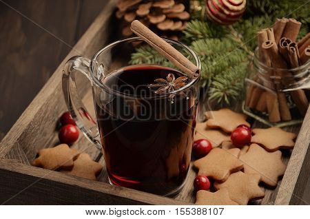 Christmas mulled wine. Holiday concept decorated with Fir branches, Gingerbread Cookies and Cranberries on dark wooden tray.  Toned image.