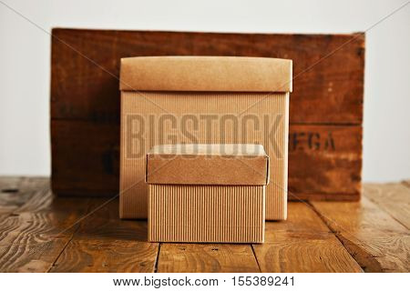 Two unlabeled paper boxes with covers standing on top of a wooden table next to a beautiful old wine box isolated on white