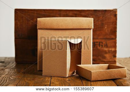 One opened and one closed beige cardboard boxes next to a rustic brown wooden crate isolated on white