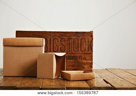 Mockup blank beige paper boxes next to a retro rough brown wooden crate isolated on white