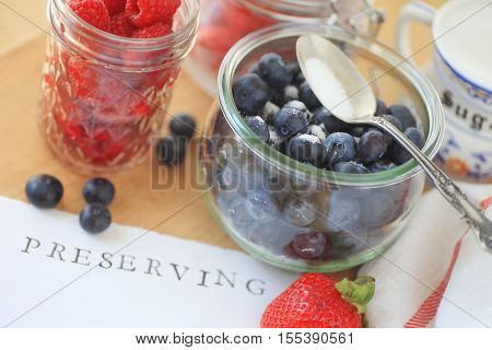 Blueberries raspberries and strawberries in glass jars with sugar ready for making jam