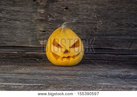 Sinister halloween pumpkin head on a wooden background