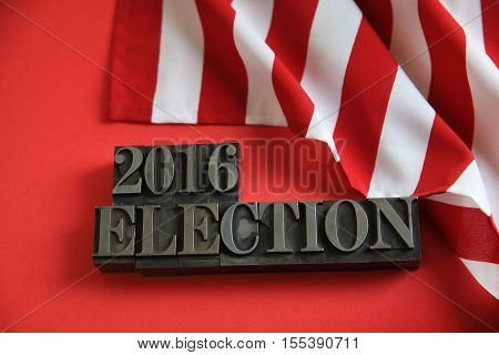 Part of an American flag with 2016 election words in metal type on a red background