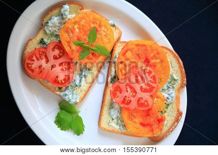 Tomato sandwich with heirloom tomatoes with cilantro mayonnaise on a white platter