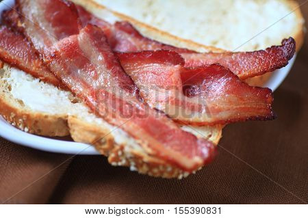Using thick-sliced bacon to make a sandwich on whole-grain bread with mayonnaise