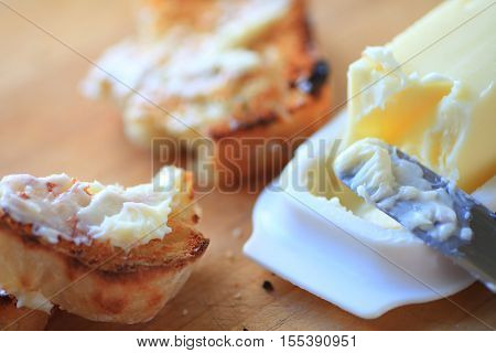 Broken slice of buttered toast with knife and butter dish
