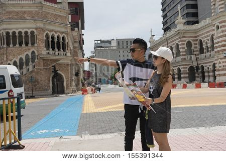 man and woman as couple look at map try to find a way in city as a tourist in foreigner country on holiday / man and woman use map