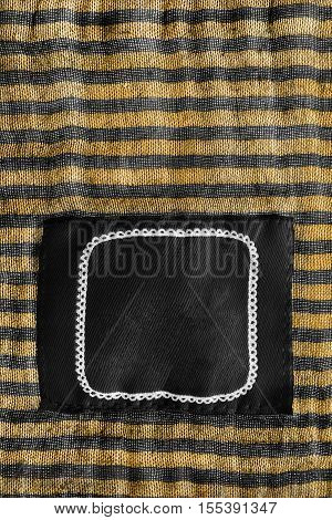 Blank clothes label on striped black and yellow cloth