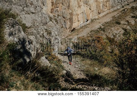 Yalta Russia - October 6 2016: young male athlete with walking poles to walk uphill on background sheer cliff during Crimea mountain marathon