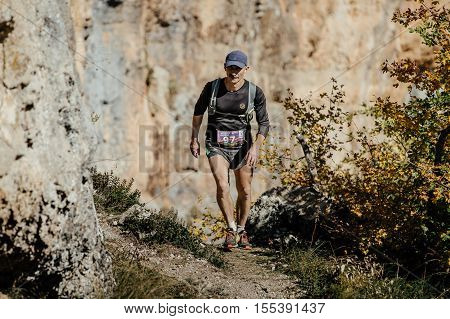 Yalta Russia - October 6 2016: middle-aged man runs on a trail with running backpack during Crimea mountain marathon