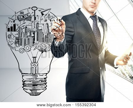 Young businessman drawing abstract lightbulb with creative financial sketch. Business idea concept