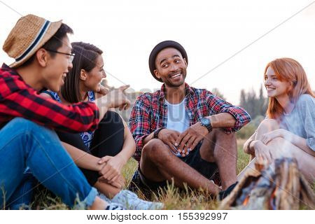 Multiethnic group of smiling young people sitting and talking near bonfire