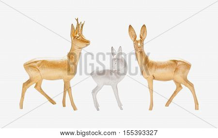 Male female and young deer in gold and silver color carved in wood isolated