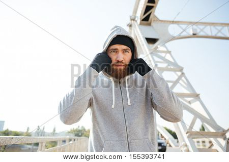 Portrait of a young sport athlete man in hoodie standing at the urban bridge
