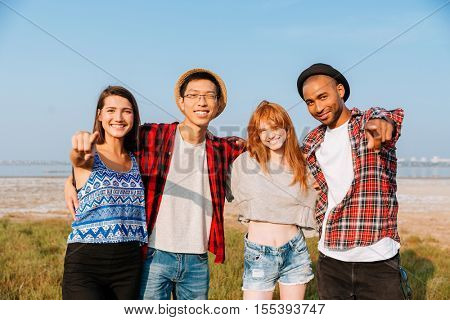 Multiethnic group of smiling young people standing together and pointing on you