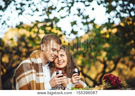 Loving couple with wine glasses embracing at autumn park.