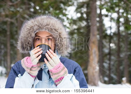 A young girl in warm winter clothes holding a cup with a drink on the background of the winter forest horizontal frame close up portrait. Christmas girl outdoor portrait. Girl drinking hot tea in the winter forest. Winter Warming Up Concept.