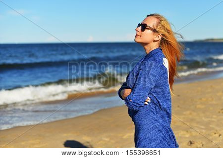 Young prett woman walking on sand beach