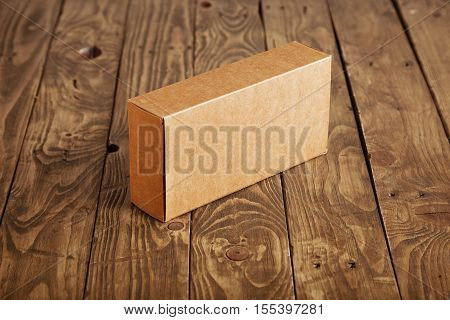 Craft cardboard package box presented on stressed brushed wooden table