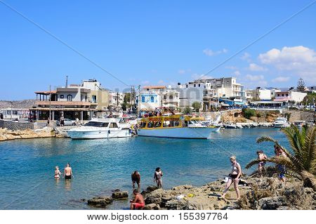 SISSI, CRETE - SEPTEMBER 14, 2016 - Tourists on the rocky shoreline with views of boats and restaurants to the rear Sissi Crete Greece Europe, September 14, 2016.