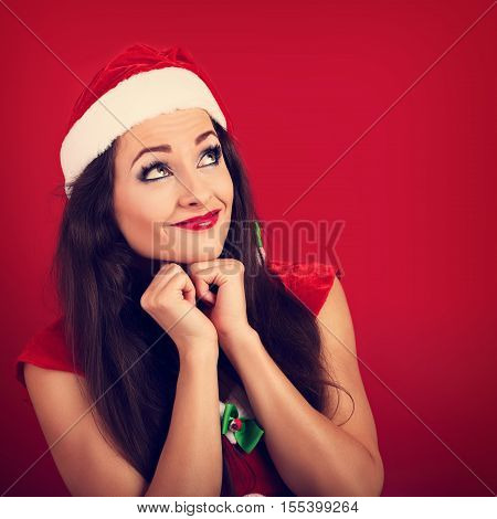 Dreaming Happy Woman In Santa Claus Christmas Costume Looking Up And Making A Wish On Red Background