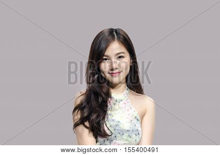 Asian woman smiling with dimple long hair black eyes on gray background