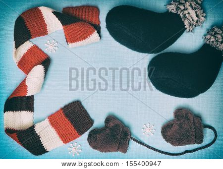 Composition of felt boots, little fur mittens, knitted scarf and small snowflakes on blue textured background. Cute winter frame with blank space for text. Christmas and New Year greeting card