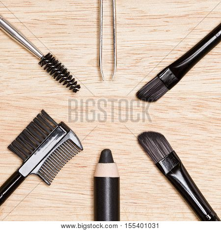 Accessories for care of brows and lashes: brow comb / brush combo, spoolie brush, angled brushes, eyebrow pencil, tweezers on wood background. Eyebrow and eyelashes grooming tools poster