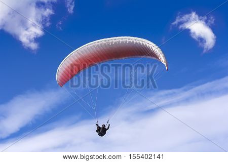 Paragliding on background of blue sky and white clouds