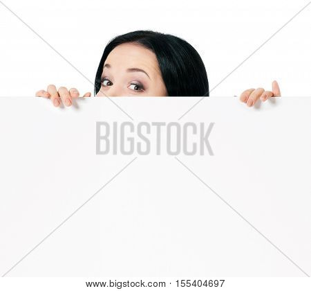 Surprised woman eyes over blank promotional display, isolated on white background. Businesswoman looking over top of white sign. Advertisement business concept - female with white blank board.
