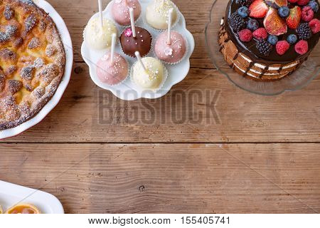 Table with naked cake decorated with chocolate and fruit, sweet pie and colorful cakepops. Studio shot on brown wooden background. Copy space. Flat lay.