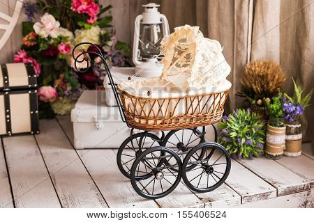 Doll's pram. Vintage doll stroller. Retro cart dolls made of rattan and white lace.