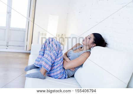 young beautiful hispanic woman in painful expression holding her belly suffering menstrual period pain lying sad on home couch having tummy cramp in female health concept