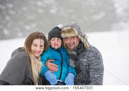 Father and mother having fun with their son, playing in the snow. Foggy white winter nature.