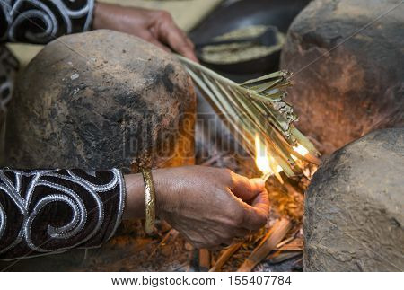 omani lady making fire in her kitchen