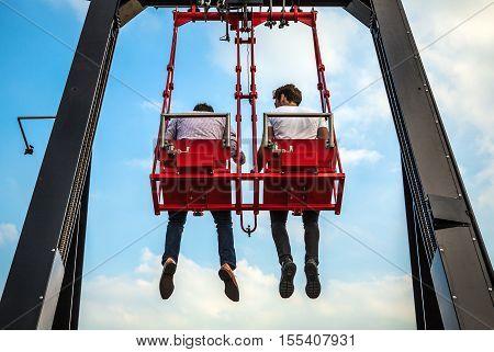 People having fun In swing carousel against blue sky.