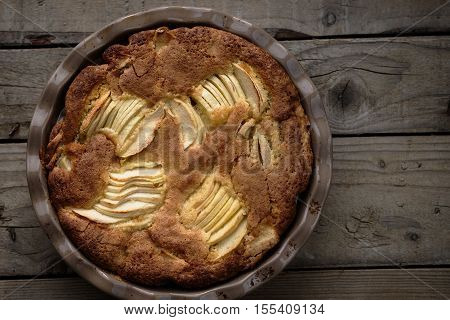 Rustic french apple pie with vanilla and rum in a round ceramic baking pan. Wooden background. Horizontal.