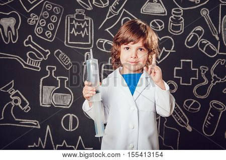 Happy little boy in doctor costume holding syringe on dark background with pattern. Lifts thumbs up.