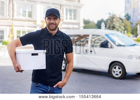 smiling carrier with pack standing in front of commercial vehicle