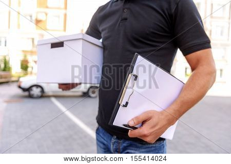 delivery man holding the box and a tablet, close up