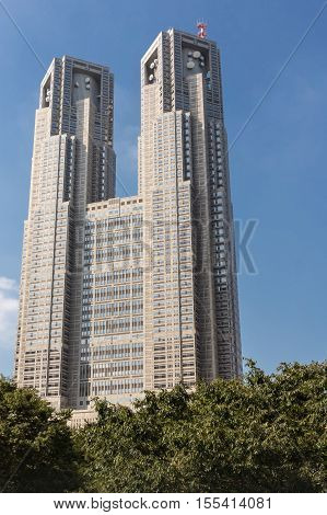 Tokyo Japan - October 2 2016: The two towers of the Tokyo Metropolitan Government building stand behind green foliage. Shinjuku neighborhood.