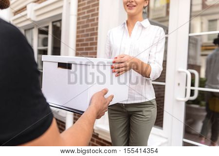 delivery man giving a box to the female customer