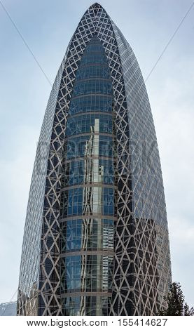 Tokyo Japan - October 2 2016: The glass-and-iron iconic Cocoon-shaped tower or Tokyo Mode Gakuen under light blue sky reflects the L-shaped skyscraper. Green foliage and other towers. Shinjuku neighborhood.