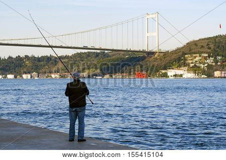 Istanbul Turkey - March 18 2013: Istanbul at the Bosphorus bonito bluefish mackerel sardines sea bass and other bottom fish hunt. Migration time increases in fishing catch fish. Showing bridge Fatih Sultan Mehmet Bridge.
