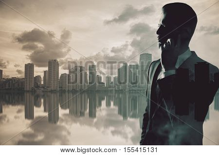 Backlit side portrait of handsome young businessman talking on mobile phone on abstract city background with copy space. Double exposure. Communication concept