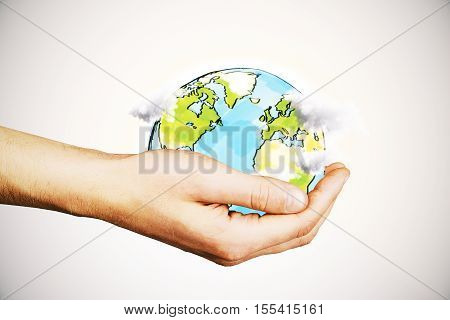 Hand holding creative drawn terrestrial globe with clouds on light background. Eco concept