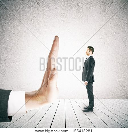 Tiny businessman in suit standing against human palm on concrete background. Denial concept