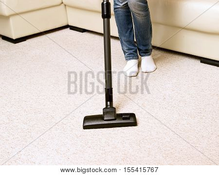 girl in jeans vacuuming the house. bright carpet and light leather sofa