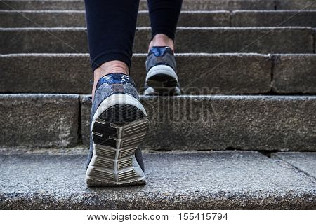 Morning jogging young woman outdoors. Running up the stairs.