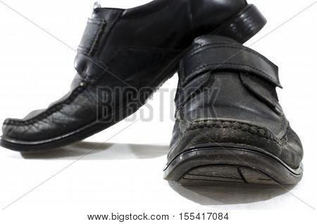 Old used and worn black leather shoes on a white background